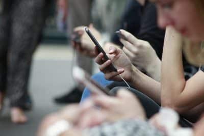 Ludzie z komórkami w dłoniach - abonament z i bez telefonu