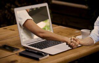 umowa pożyczki zawierana na odległość - komputer i uściśnięte dłonie