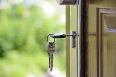 Drzwi do domu z kluczami w zamku - pożyczka czy kredyt?