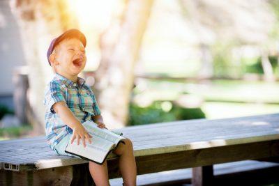Dziecko na ławce z książką i pełne radości
