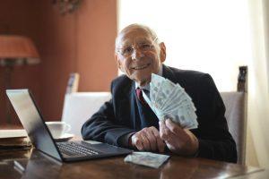 Emeryt z gotówką w ręku z 14 emerytury - komputer, biurko