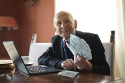 """Emeryt z trzynastą emeryturą - tzw. """"jarkowym"""" - gotówka w ręki i komputer, za biurkiem"""