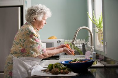 Babcia emerytka myjąca marchewkę - wydatki bieżące - kredyt