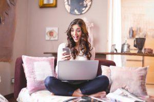 Kobieta z telefonem w ręku - pozytywny wniosek pożyczkowy