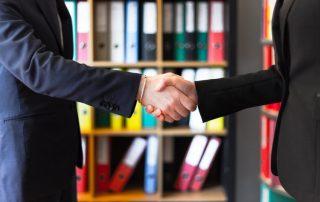 Kredyt kupiecki - umowa - uściśnięte dłonie biznesmena i bizneswoman