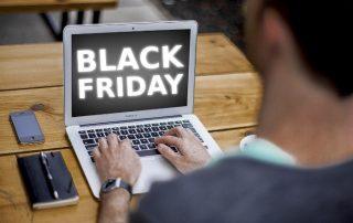 Black Friday - mężczyzna przy komputerze szukający promocji i pożyczki na nie