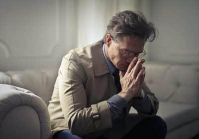 Mężczyzna długami - smutny, ręce przy głowie