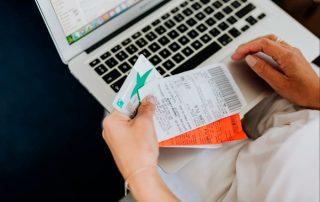 Osoba płacąc wysokie rachunki za wydatki kartą debetowę i komputer