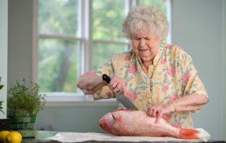 Starsza pani z nożem i niską emeryturą - ryba