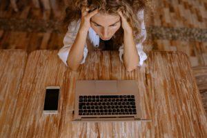 Kobieta przed komputerem z telefonem - brak zdolności kredytowej i ręce na głowie