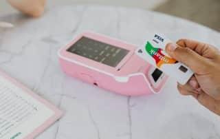 Terminal płatniczy i karta w dłoni, marmurkowy stół - płatność