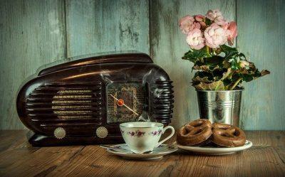 Odbiornik radiowy z filiżanką i ciastkami w tle