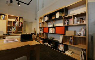 biuro w domu prywatnym - regał z książkami i stół