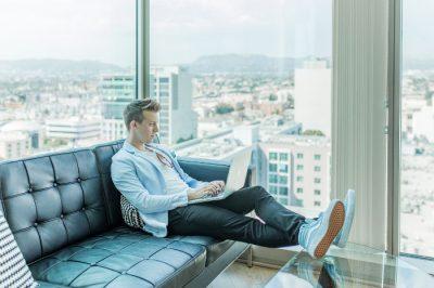 Mężczyzna na home office - z laptopem na kanapie