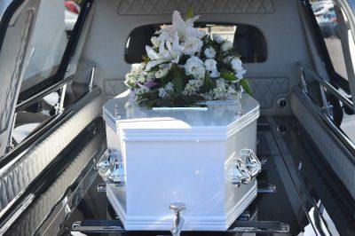 Biała trumna w karawanie - zasiłek pogrzebowy