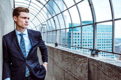 Młody pracownik - mężczyzna w garniturze - zamyślony na dachu