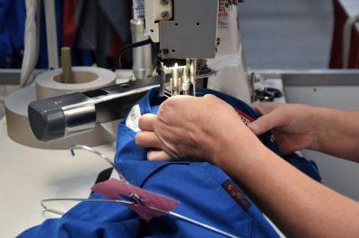 Szwaczka szyjąca koszulę pod maszyną do szycia