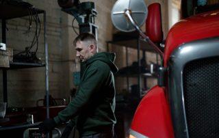 Kierowca zawodowy przy ciężarówce w warsztacie