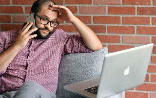 sfrustrowany i zestresowany pracownik na kanapie - z telefonem i laptopem