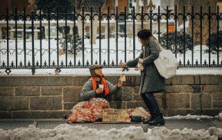 Biedak na ulicy żebrzący na ulicy - kobieta wręczająca mu pieniądze