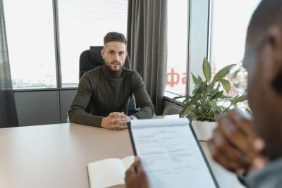 Rekruter i kandydat podczas rozmowy kwalifikacyjnej w biurze przy stole