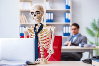Nieznośny szef nad wymęczonym pracownikiem - kościotrupem przy komputerze