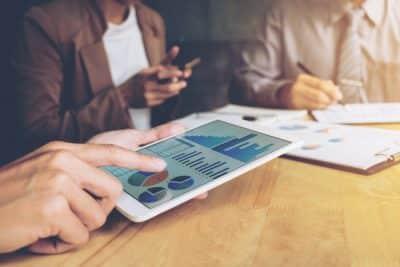 Giełdowe wykresy na tablecie - inwestorzy na zebraniu - konsensus rynkowy