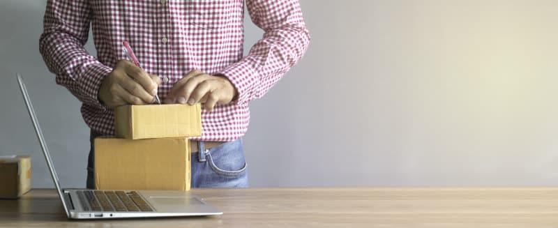 Przedsiębiorca pakujący paczkę dla klienta - laptop na stole i zamówienie