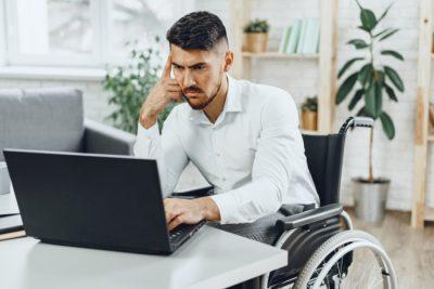 Pracownik niepełnosprawny przy komputerze - wózek inwalidzki